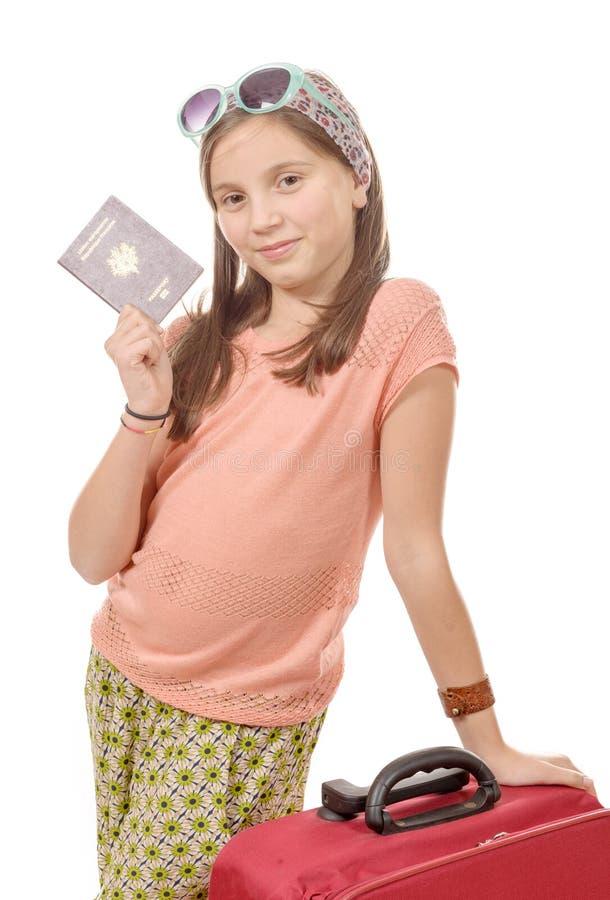 Muchacha sonriente con el bolso del viaje, pasaporte aislado sobre blanco foto de archivo