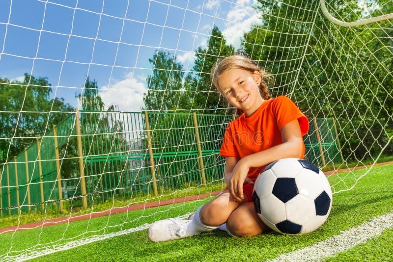 Muchacha sonriente con el brazo de doblez en la sentada del fútbol fotos de archivo