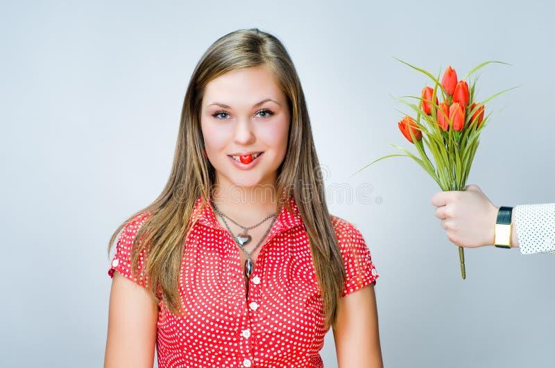 Muchacha sonriente con el caramelo en forma de corazón foto de archivo