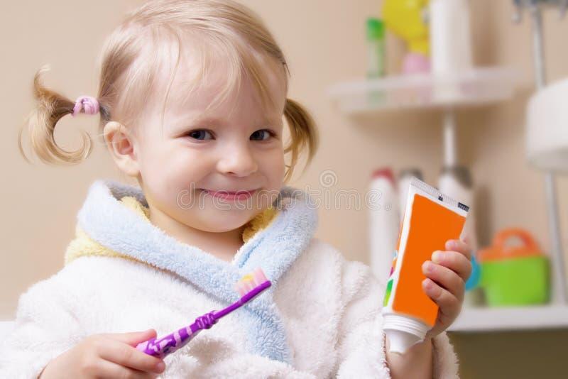 Muchacha sonriente con el cepillo de dientes y el tubo imagen de archivo
