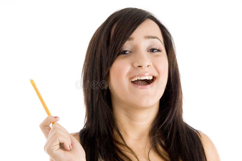 Muchacha sonriente con el lápiz que mira la cámara fotografía de archivo libre de regalías
