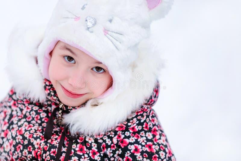 Muchacha sonriente con el sombrero de piel blanco como un gato Fondo nevoso del invierno imagen de archivo