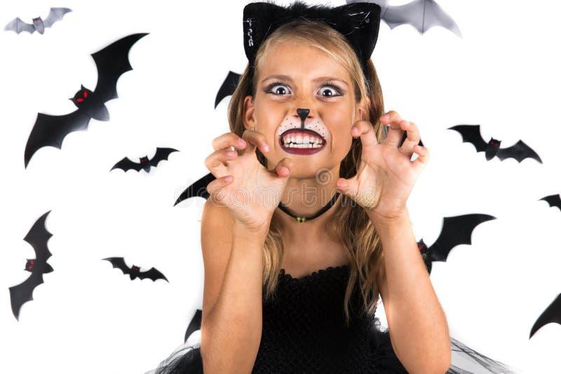 Muchacha sonriente con el traje del gato negro, maquillaje de Halloween en el partido de Halloween, remiendo de la calabaza Niños fotos de archivo libres de regalías