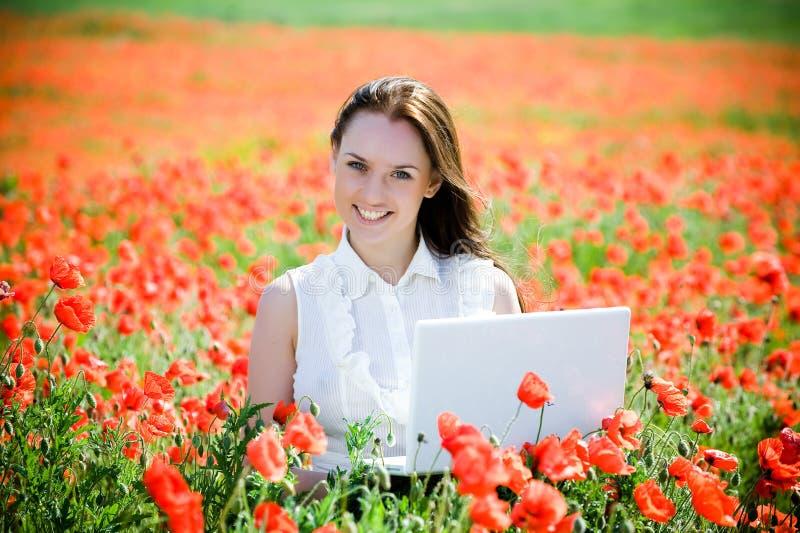 Muchacha sonriente con la computadora portátil fotografía de archivo