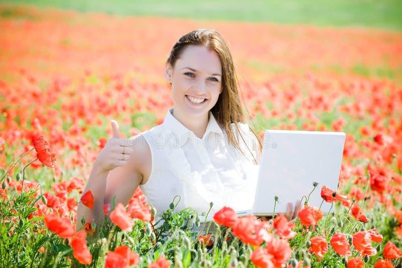Muchacha sonriente con la computadora portátil foto de archivo