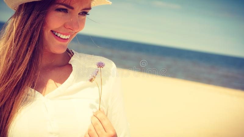 Muchacha sonriente con la flor en la playa imagenes de archivo