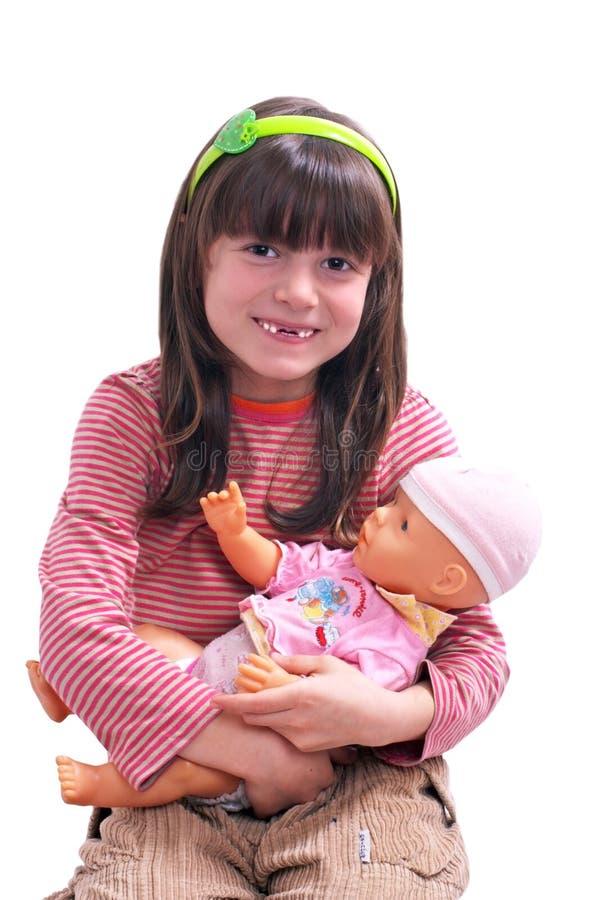 Muchacha sonriente con la muñeca foto de archivo libre de regalías