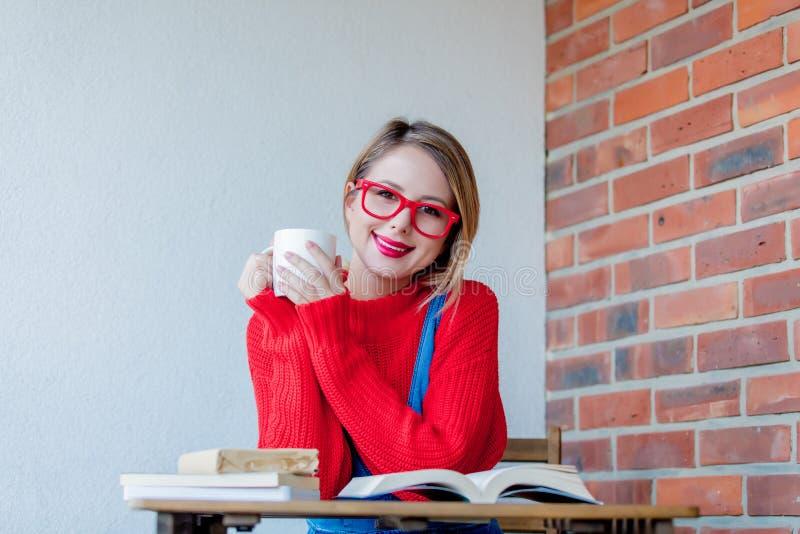 Muchacha sonriente con la taza de café y de libros fotografía de archivo