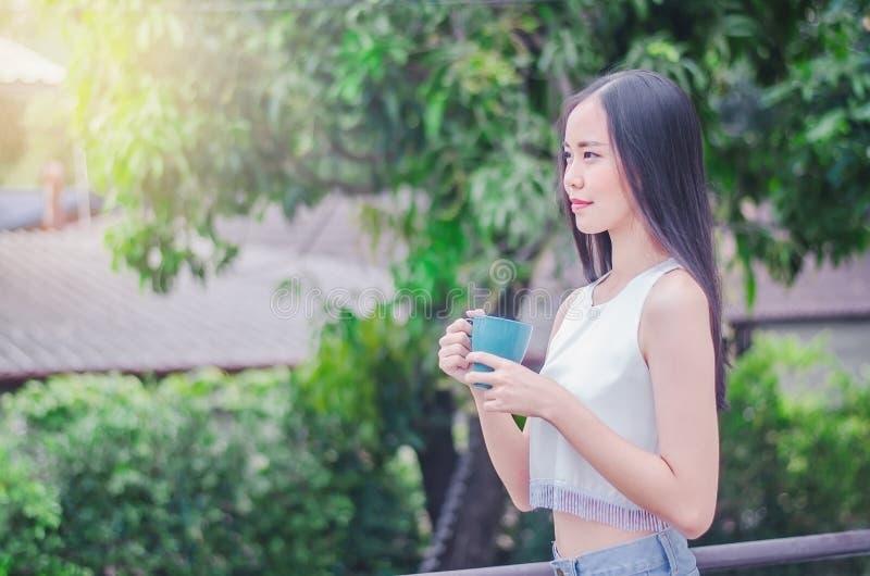 Muchacha sonriente con la taza de t? o de caf? que goza cerca de ?rbol del parque en luz del sol de la ma?ana fotografía de archivo libre de regalías