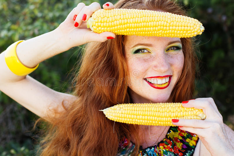 Muchacha sonriente con las pecas que sostienen la mazorca de maíz imagen de archivo libre de regalías