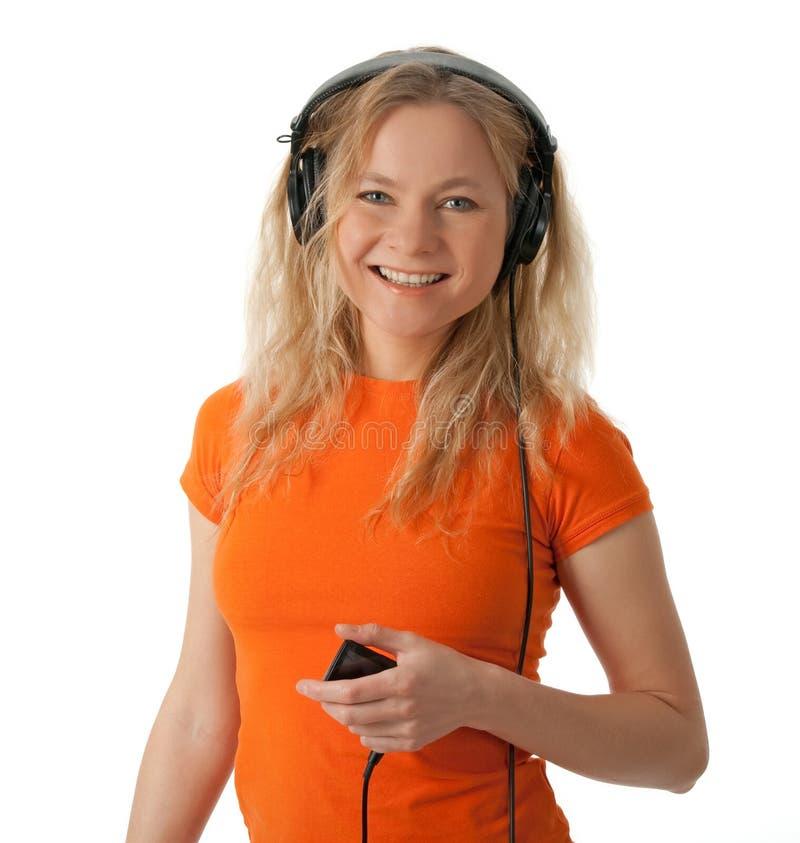Muchacha sonriente con los auriculares y el jugador mp3 foto de archivo libre de regalías