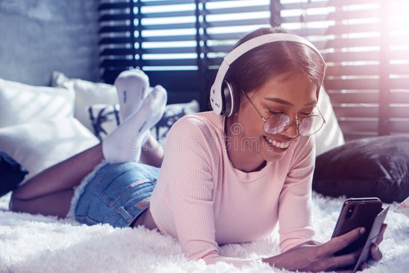 Muchacha sonriente con los auriculares y móvil que escuchan la música mientras que se relaja en su cama en casa fotos de archivo
