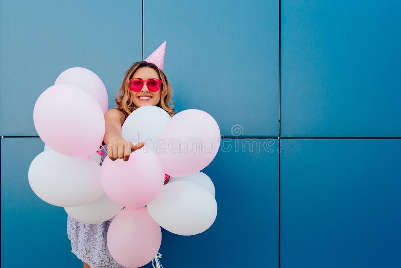 Muchacha sonriente con los balones de aire que muestran un pulgar para arriba imagen de archivo libre de regalías