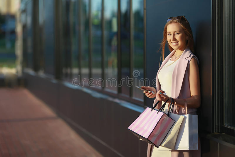 Muchacha sonriente con los panieres con el teléfono a disposición Comprador ventas imagenes de archivo