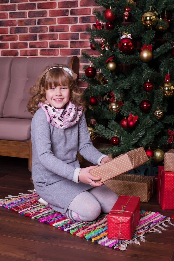 Muchacha sonriente con los regalos que se sientan cerca del árbol de navidad imagen de archivo libre de regalías