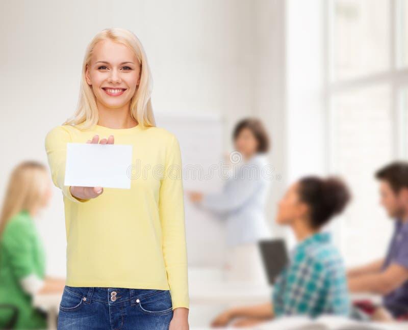 Muchacha sonriente con negocio en blanco o la tarjeta de presentación imagen de archivo