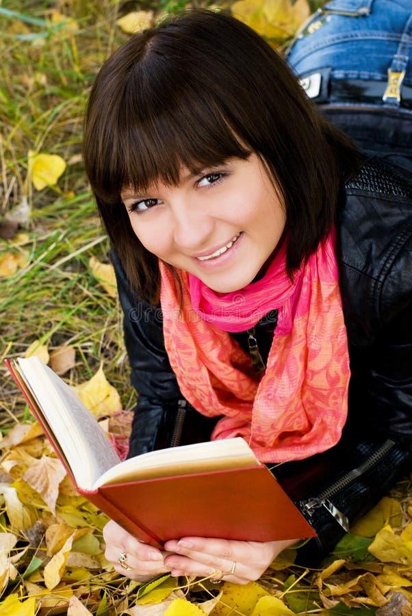 Muchacha sonriente con un libro en el parque fotografía de archivo libre de regalías