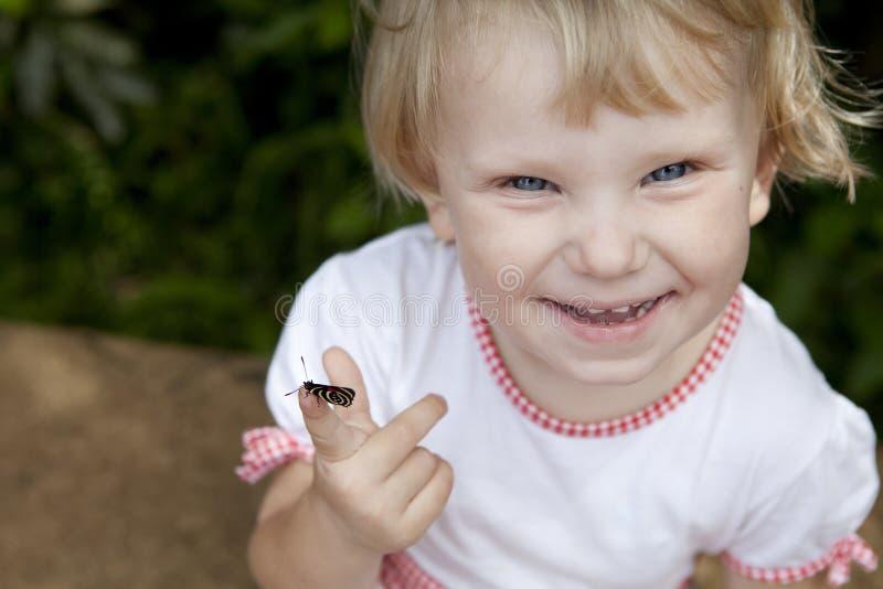 Muchacha sonriente con una mariposa en el dedo imagen de archivo libre de regalías