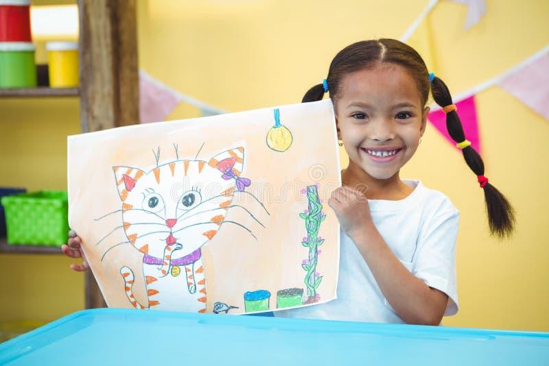 Muchacha sonriente con una pintura de su gato imagen de archivo