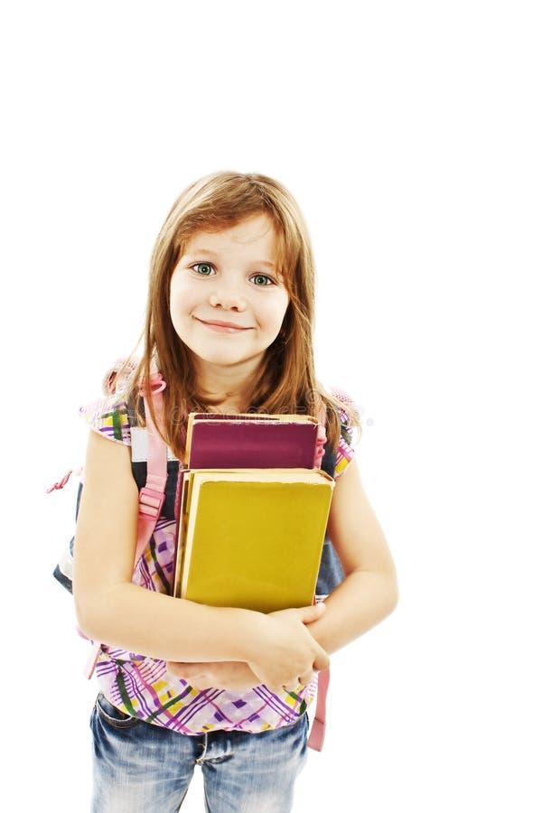 Muchacha sonriente de la escuela con los libros de la explotación agrícola de la mochila foto de archivo libre de regalías