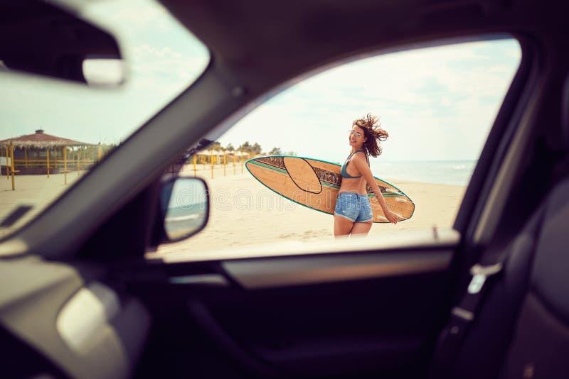 Muchacha sonriente de la persona que practica surf de la mujer en bikini con la tabla hawaiana que camina en la playa imagenes de archivo