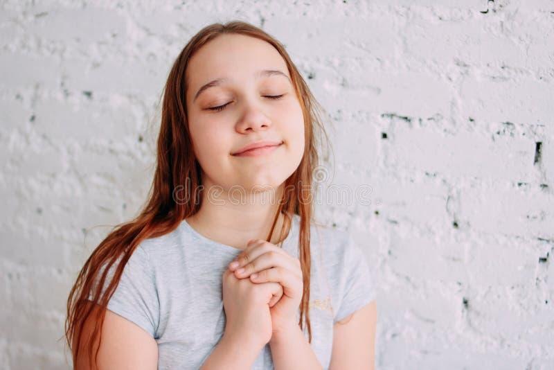 Muchacha sonriente del adolescente del pelirrojo encantador hermoso que se cierra los ojos y que hace un deseo aislado en la pare fotos de archivo libres de regalías