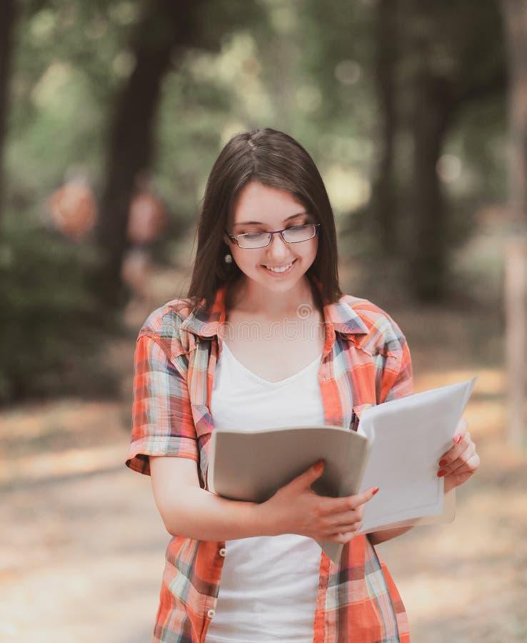 Muchacha sonriente del estudiante con un tablero en el fondo del parque imagenes de archivo