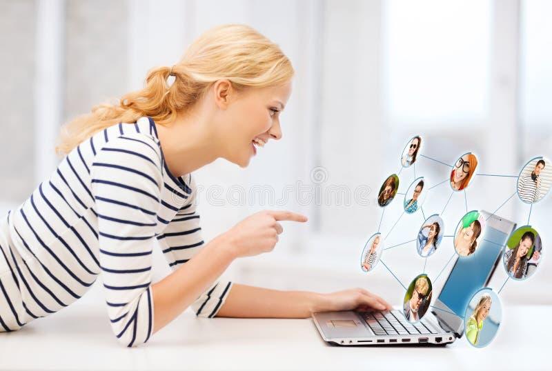 Muchacha sonriente del estudiante que señala su finger en el ordenador portátil foto de archivo libre de regalías