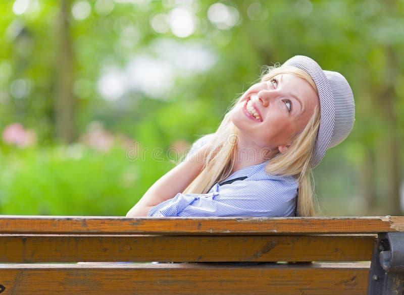 Muchacha sonriente del inconformista que se sienta en banco en el parque de la ciudad foto de archivo libre de regalías