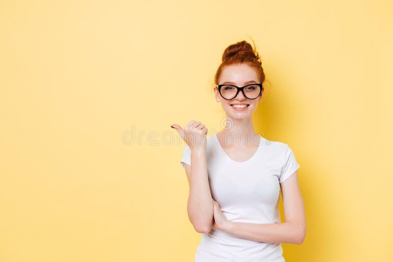 Muchacha sonriente del jengibre en lentes que señala lejos imagen de archivo