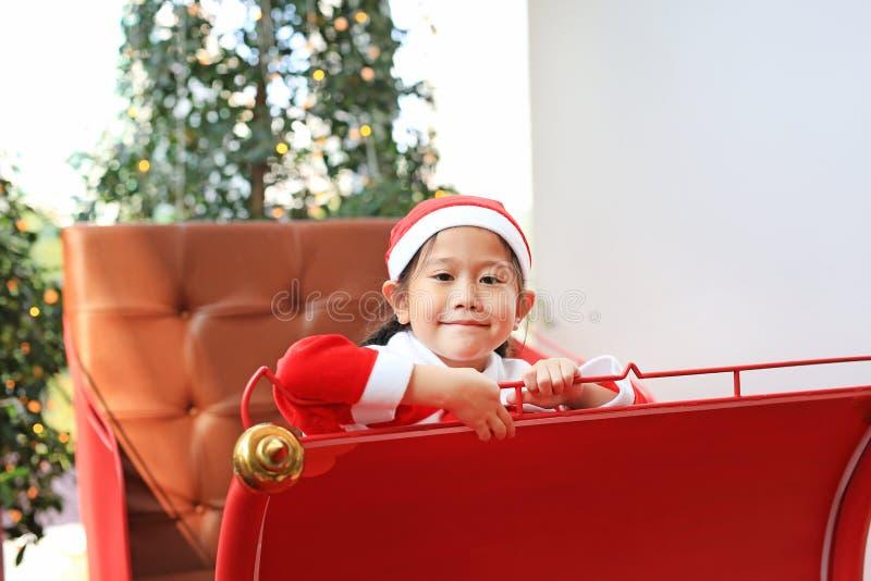 Muchacha sonriente del niño en el vestido del traje de santa que se sienta en fondo rojo de la Navidad del trineo Feliz Navidad y foto de archivo libre de regalías