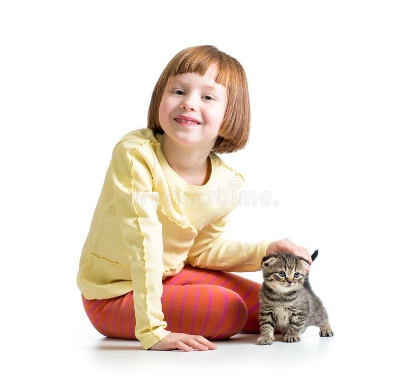 Muchacha sonriente del niño que juega con el gatito del gato imágenes de archivo libres de regalías