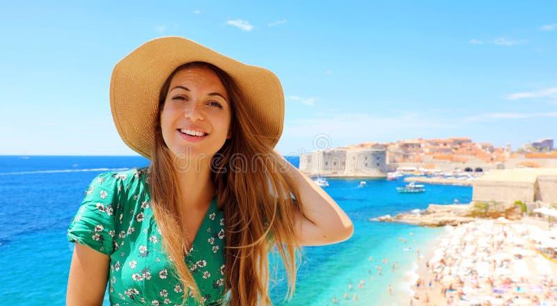 Muchacha sonriente del viajero con el sombrero en Croacia Mujer joven feliz que visita la ciudad vieja de Dubrovnik en el mar Med imágenes de archivo libres de regalías