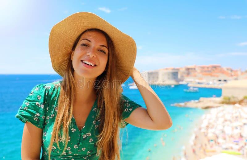 Muchacha sonriente del viajero con el sombrero en Croacia Mujer joven feliz que visita la ciudad vieja de Dubrovnik en el mar Med imagen de archivo libre de regalías