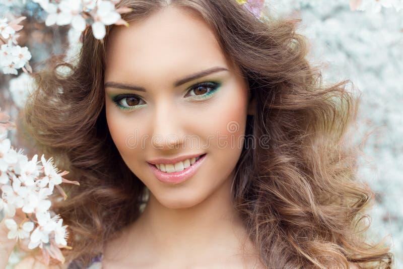 Muchacha sonriente dulce blanda joven atractiva hermosa en un jardín florecido con maquillaje hermoso foto de archivo