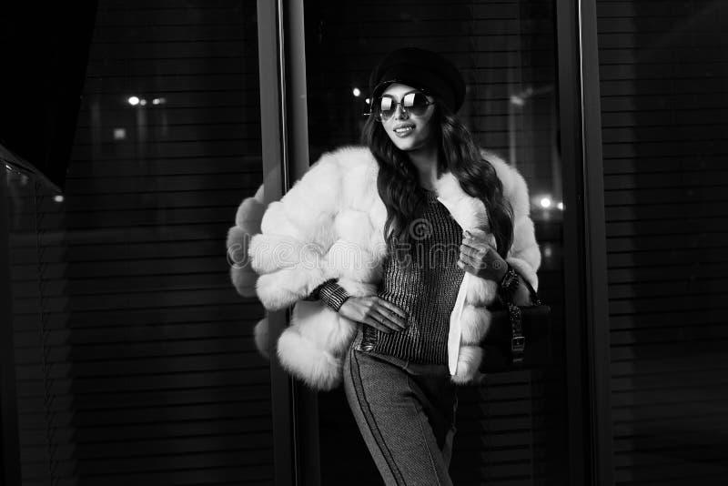 Muchacha sonriente en abrigo de pieles y gafas de sol blancos de moda foto de archivo libre de regalías