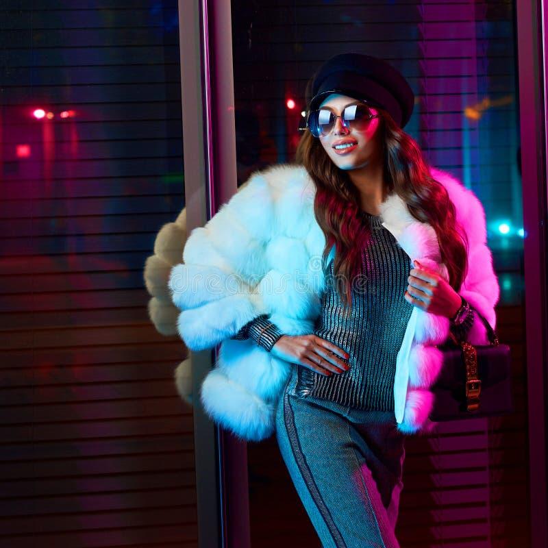 Muchacha sonriente en abrigo de pieles y gafas de sol blancos de moda fotos de archivo libres de regalías