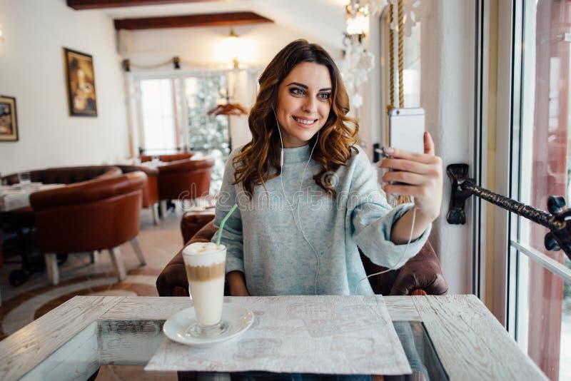 Muchacha sonriente en café que habla en la charla video en el teléfono elegante fotos de archivo libres de regalías