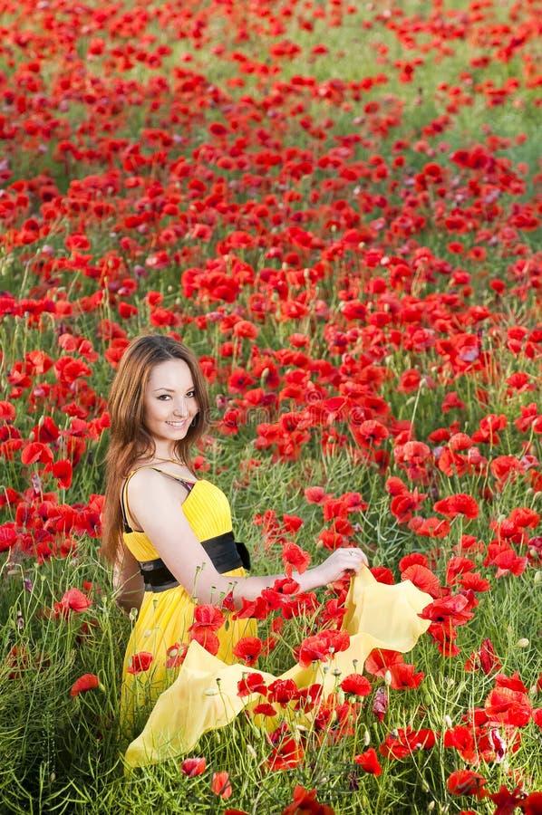 Muchacha sonriente en campo de la amapola foto de archivo libre de regalías