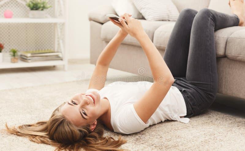 Muchacha sonriente en casa que charla en línea en smartphone foto de archivo