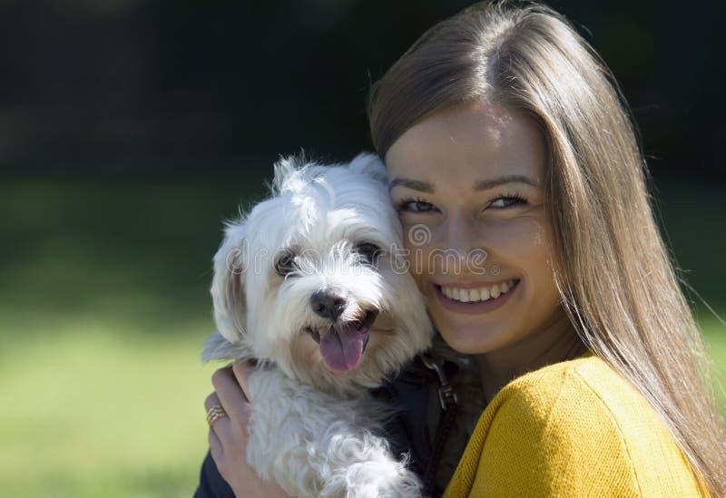 Muchacha sonriente en el abrazo de un pequeño perro blanco Una sonrisa grande en su cara foto de archivo libre de regalías