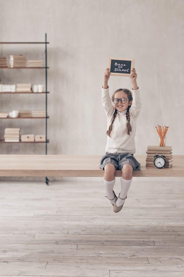 Muchacha sonriente en el escritorio imagenes de archivo