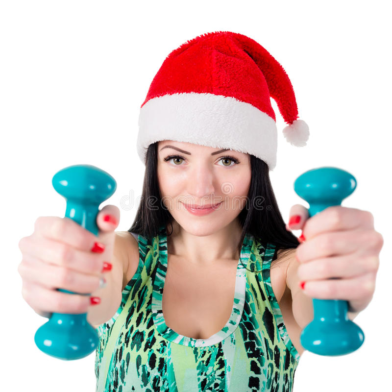 Muchacha sonriente en el sombrero de Santa Claus que hace ejercicios con pesa de gimnasia imagenes de archivo