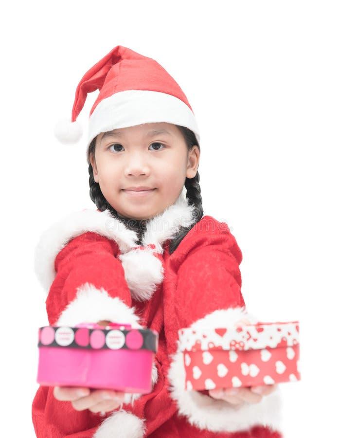 Muchacha sonriente en el sombrero rojo de santa con el regalo de la Navidad imagen de archivo