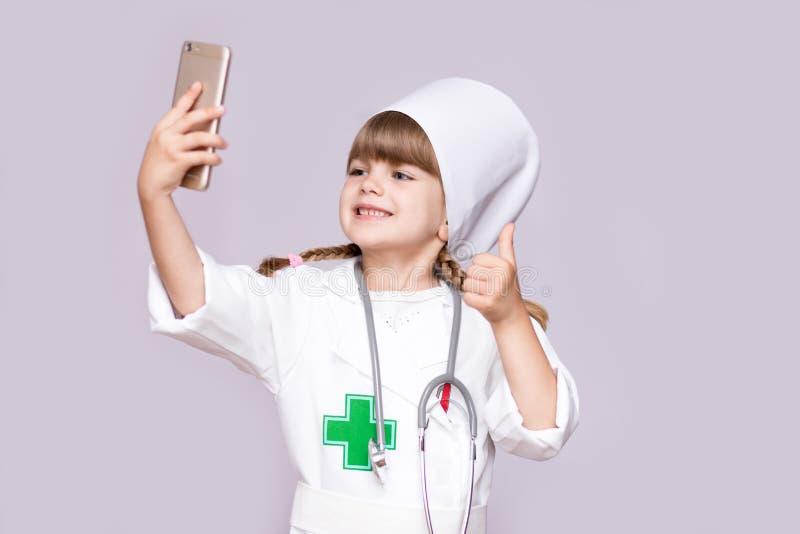 Muchacha sonriente en selfie uniforme médico del smartphone que se sostiene y de la toma fotografía de archivo