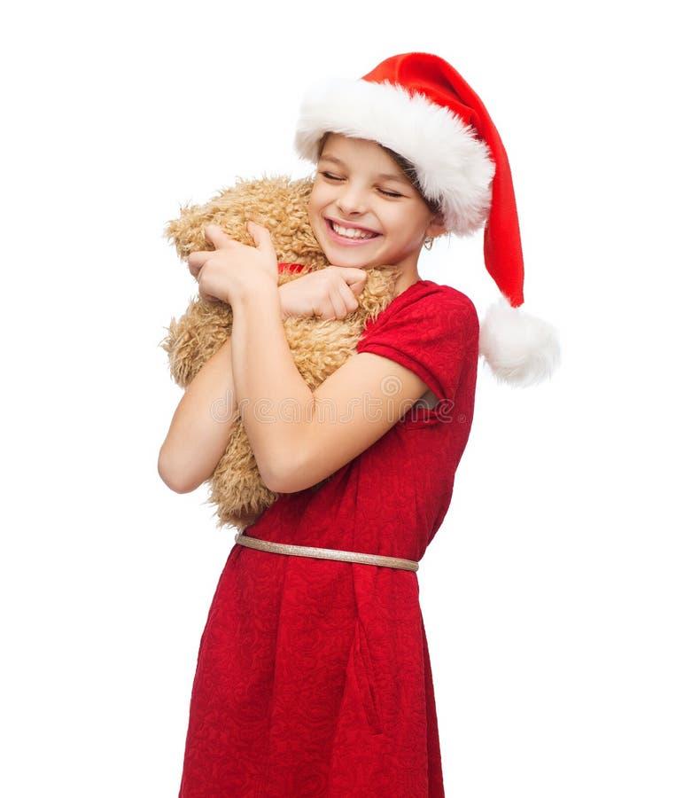 Muchacha sonriente en sombrero del ayudante de santa con el oso de peluche imagenes de archivo
