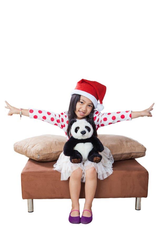 Muchacha sonriente en sombrero del ayudante de santa con el oso de peluche fotos de archivo libres de regalías