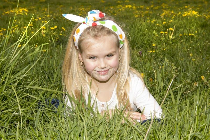 Muchacha sonriente en un claro entre las flores foto de archivo