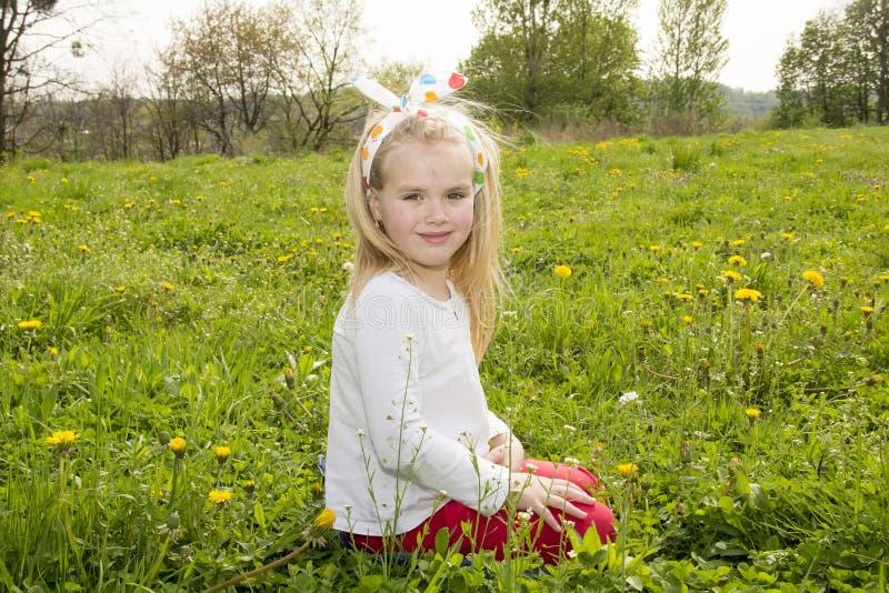 Muchacha sonriente en un claro entre las flores imágenes de archivo libres de regalías