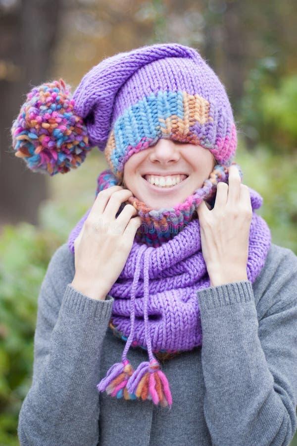 Muchacha sonriente en un sombrero hecho punto imagenes de archivo